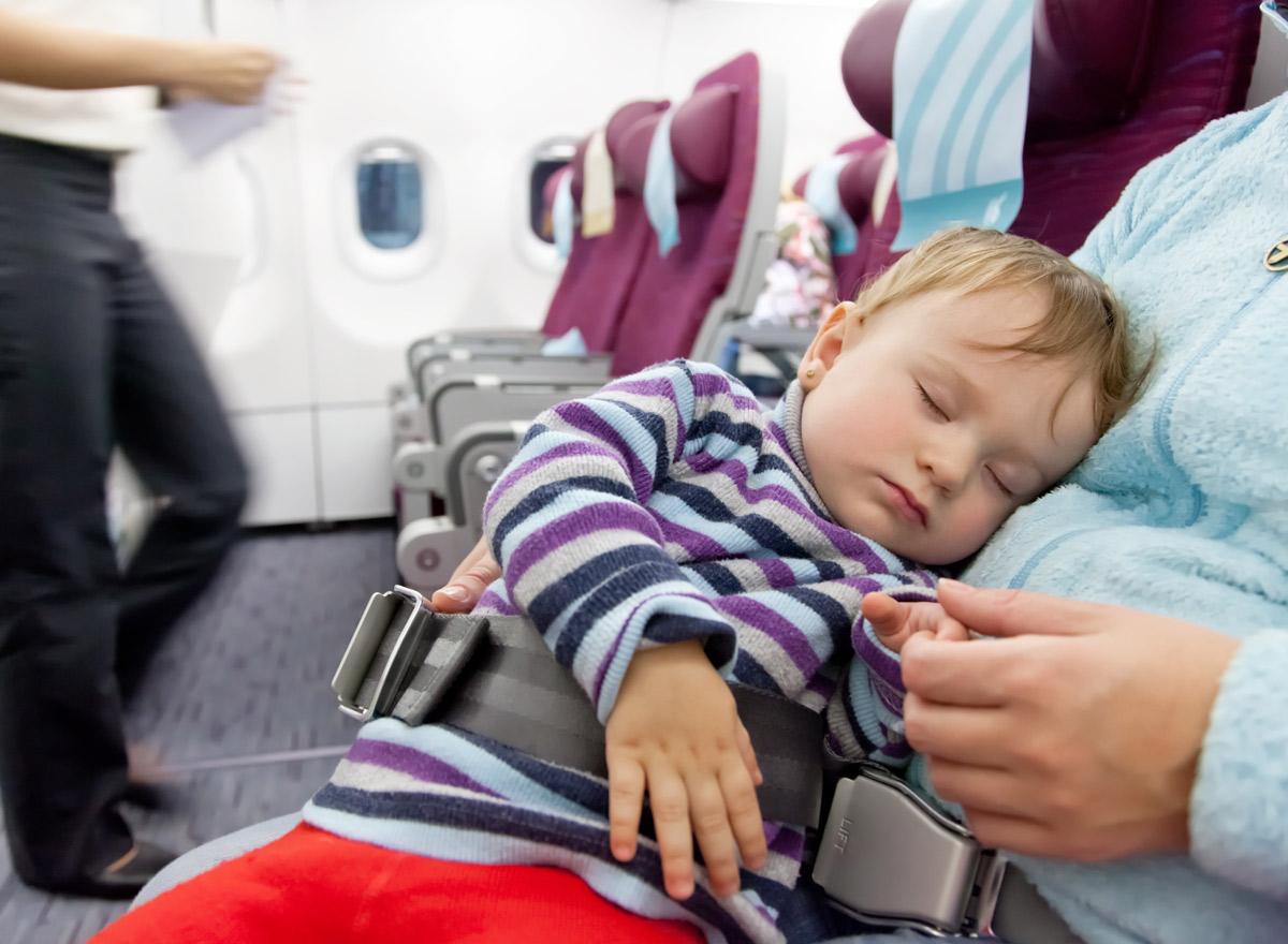 Ein Kind sitzt im Schoß der Mutter in einem Flugzeug