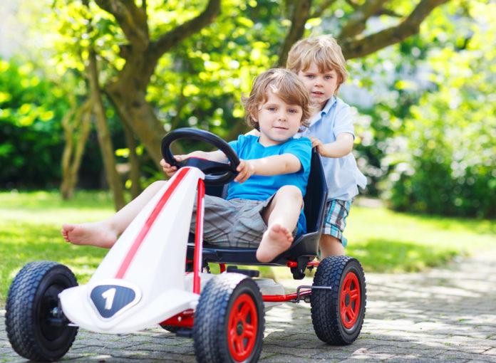 Kinder spielen mit einem Kettcar