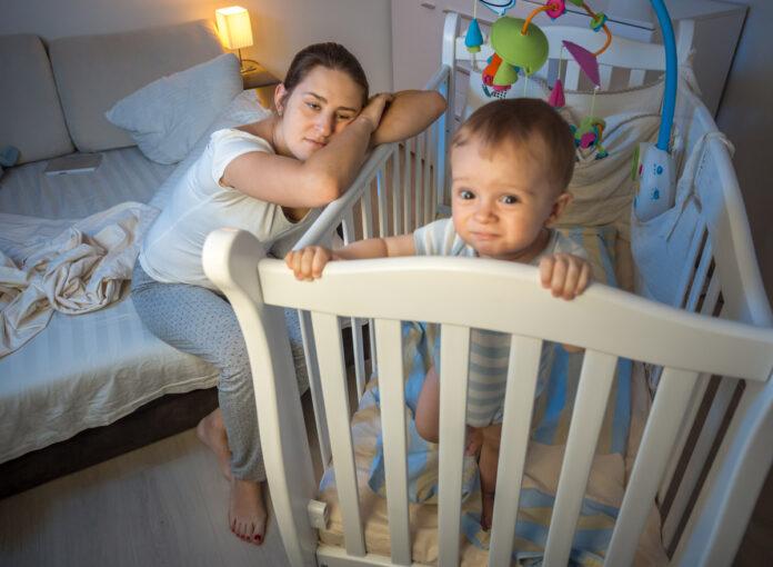 Schlaflose Mutter wacht am Babybett