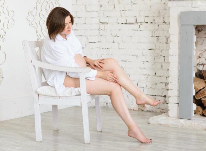 Schwangere Frau legt Beine hoch